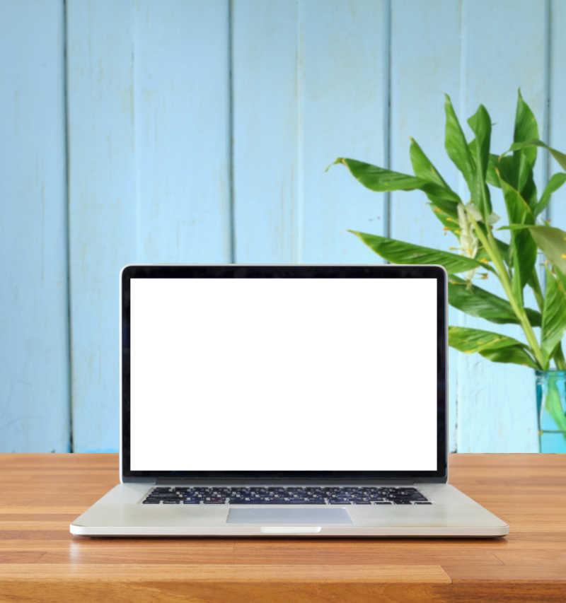 模拟蓝色墙前木桌上的笔记本电脑屏幕