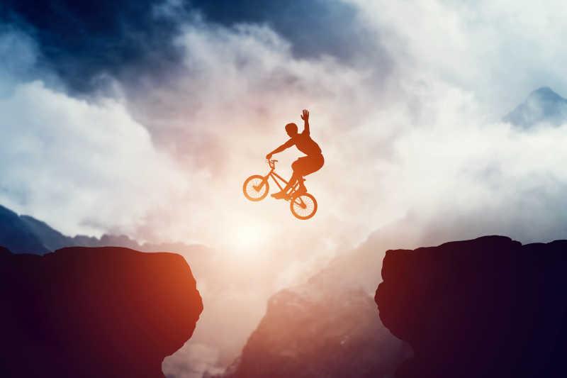 男子BMX自行车在山区日落跳悬崖