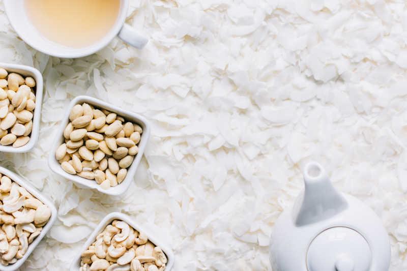 白色背景下的散落的椰蓉上的碗装腰果和茶水