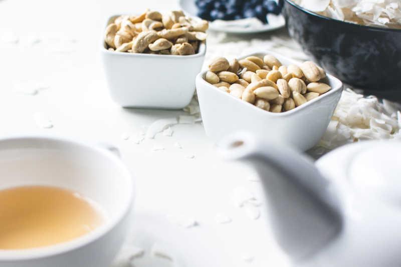 白色桌面上的碗装腰果和茶水