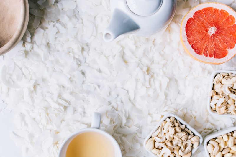 白色背景上的白色椰蓉、茶水和腰果