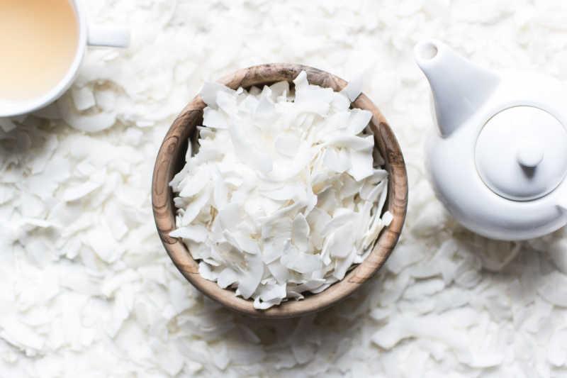白色椰蓉背景下的碗装椰蓉和茶水
