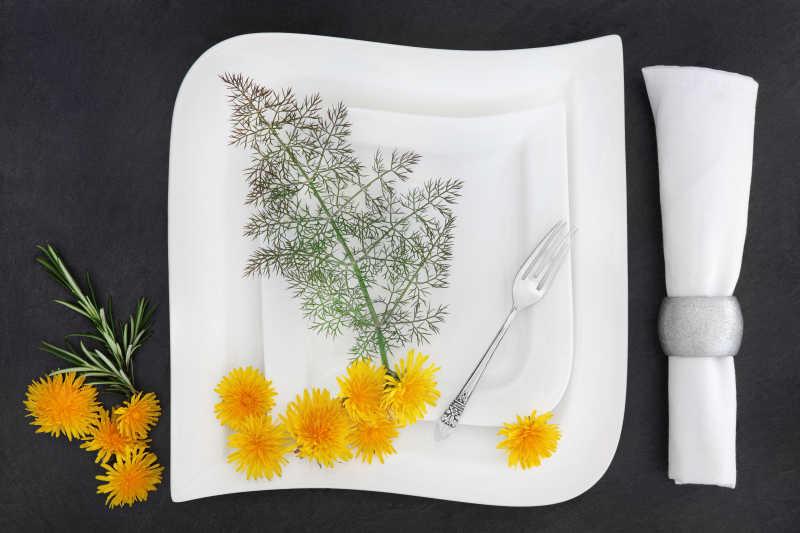 棕色桌面上的餐具和黄色花朵