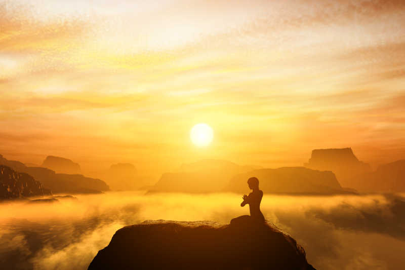 日落时分坐在山顶上练习瑜伽