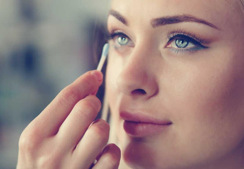 美女使用棉签化妆眼睫毛