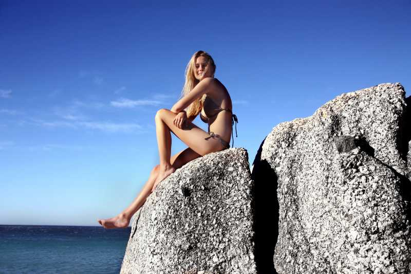 坐在岩石上的比基尼美女