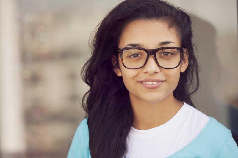 戴眼镜微笑的印度年轻女子