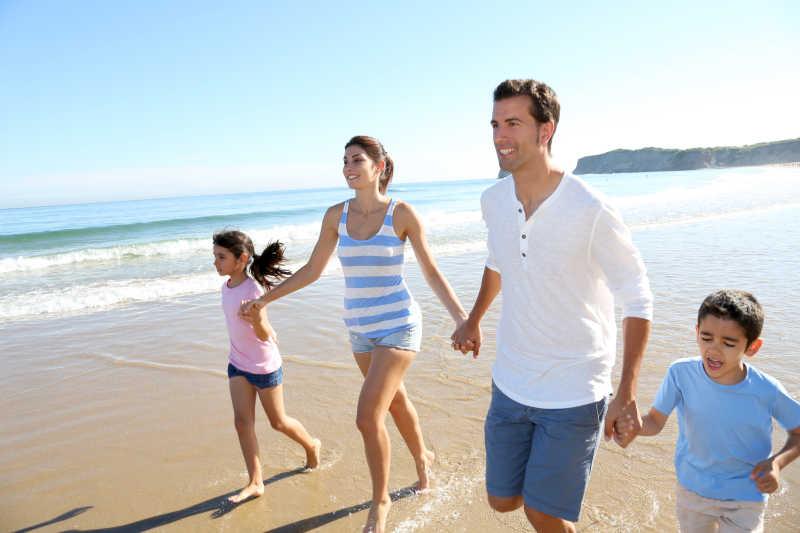 在海滩上快乐的跑步的家庭