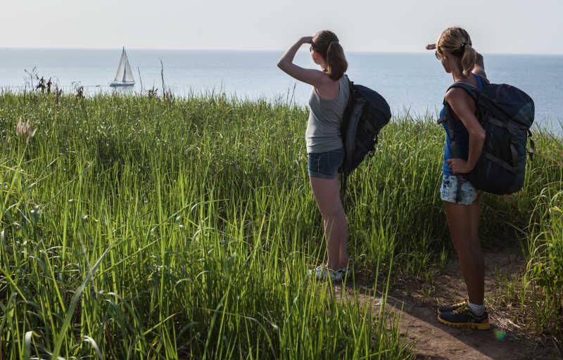 徒步旅行者在眺望海上的帆船