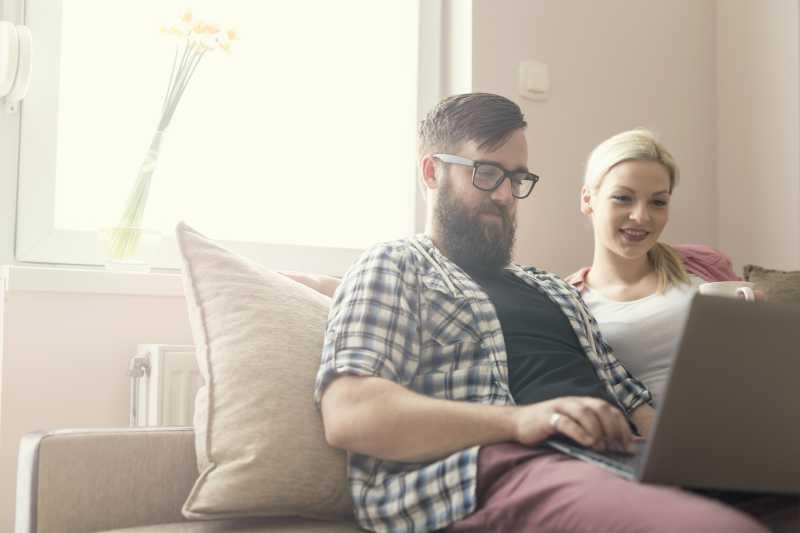 坐在沙发上使用笔记本电脑上网的夫妇