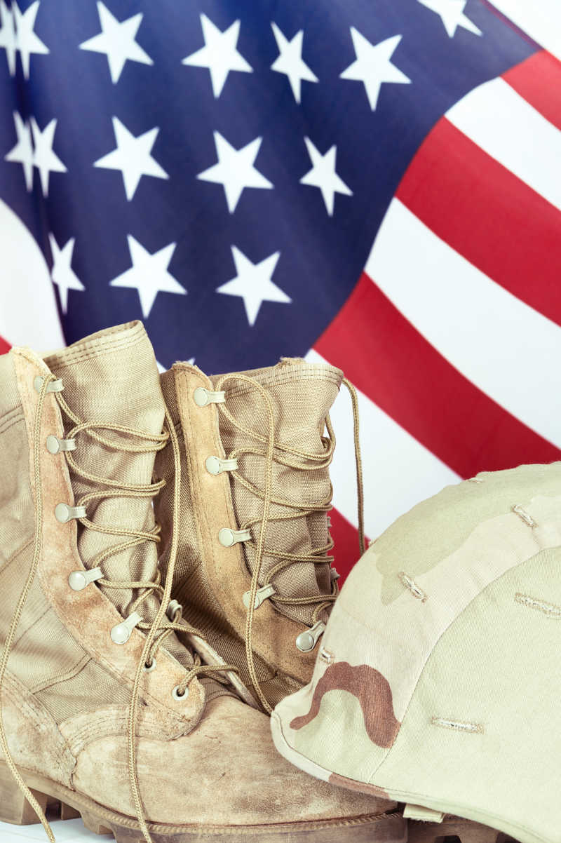 旧靴子和背景中的美国国旗帽