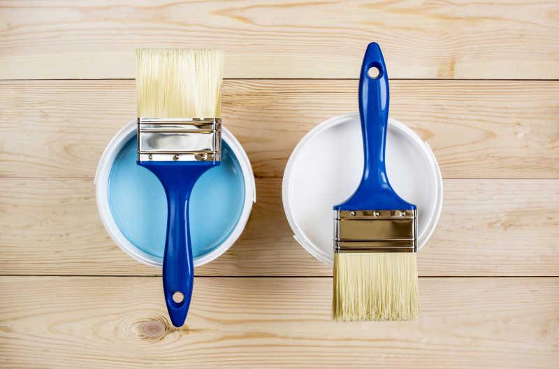 蓝色和白色油漆罐上的两个毛刷