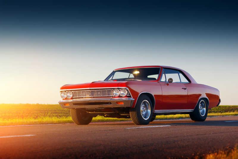 夕阳红色的老爷车停留在柏油路上
