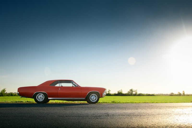 日落时分站在柏油路上的复古老爷车