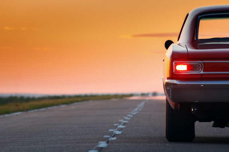 日落时分站在柏油路上的复古红色汽车