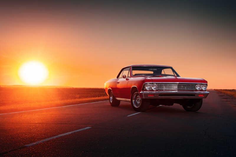 日落时分在柏油路上的复古红色汽车
