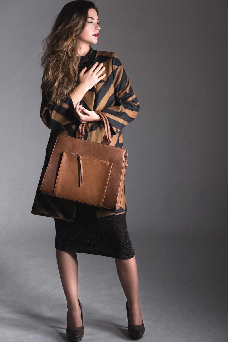 拿着包的时装美女模特