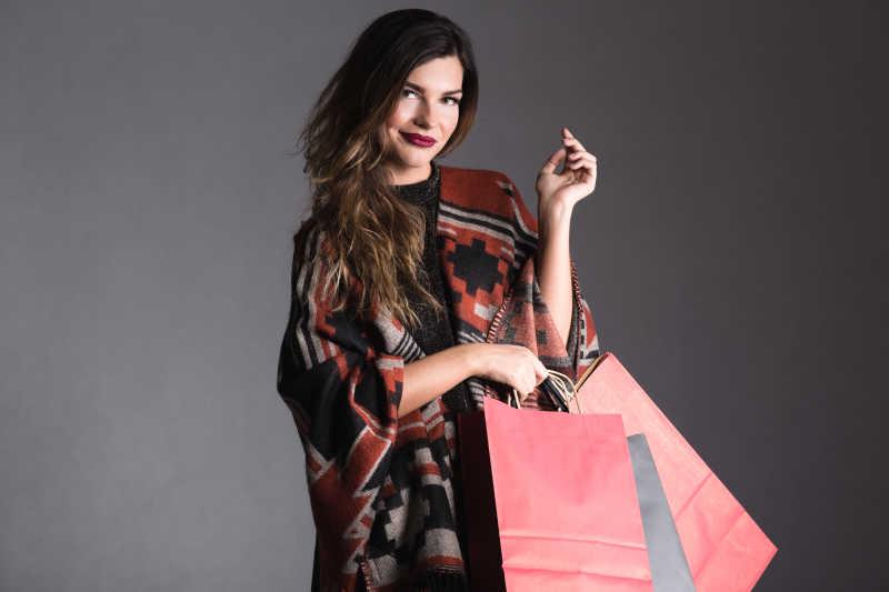 灰色背景下拿着许多购物袋的时尚妇女