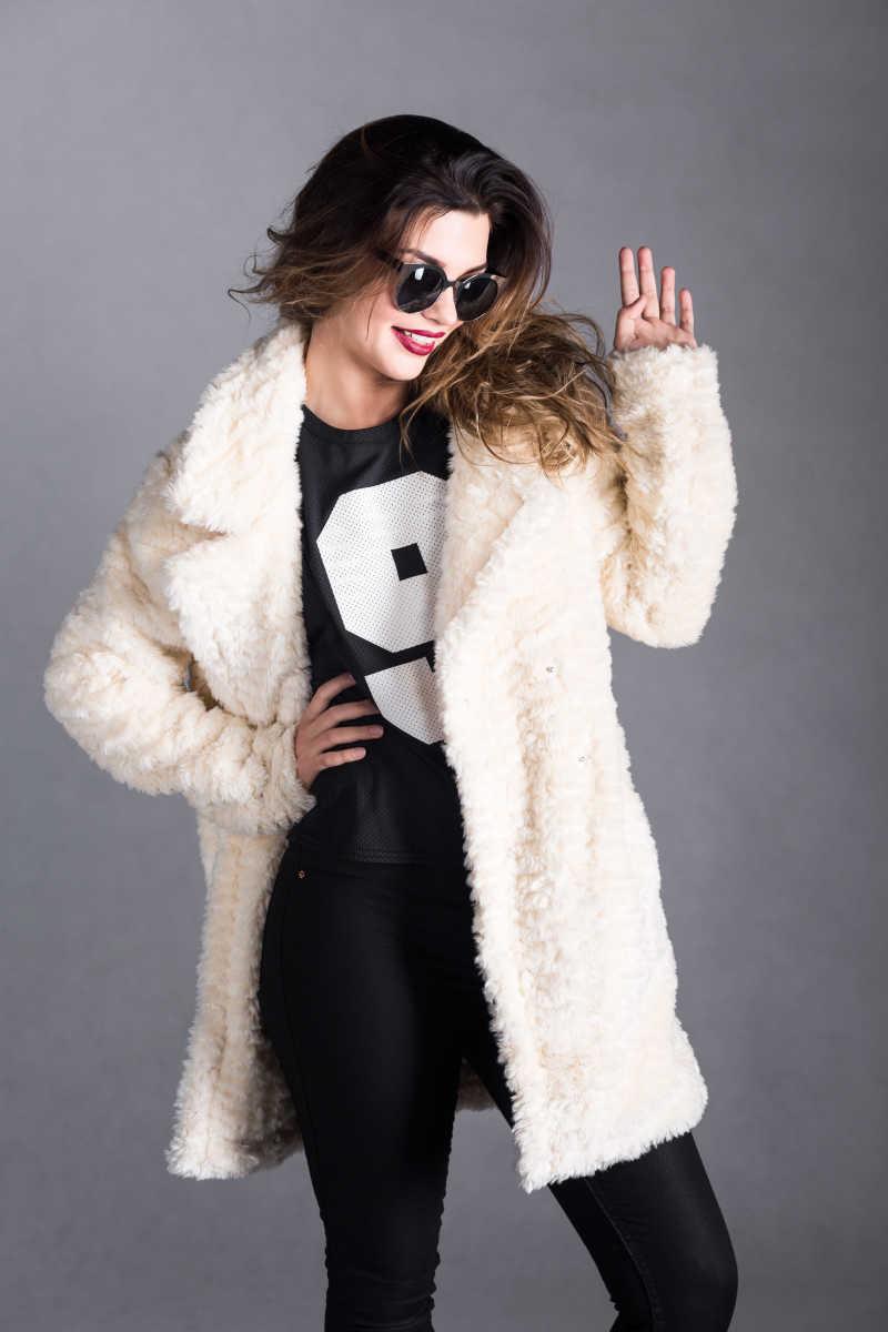 穿着冬衣带着墨镜的时装美女