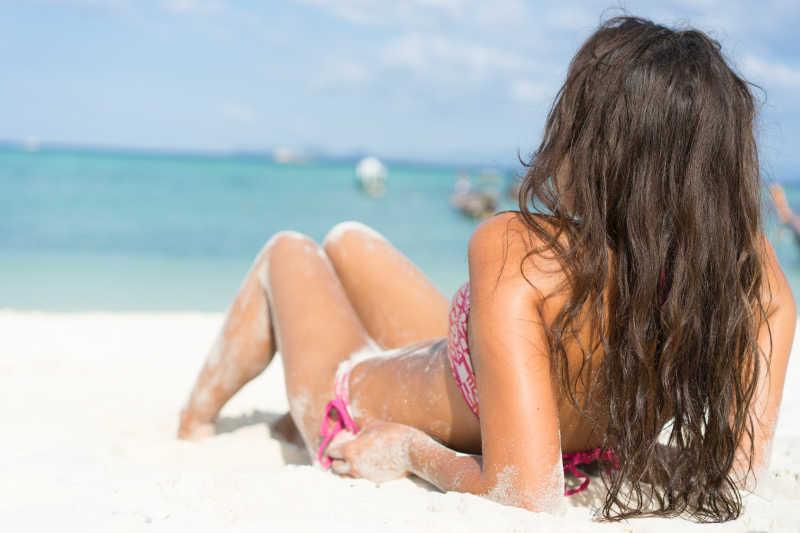 蓝色的海边沙滩上穿着比基尼晒日光浴的美女