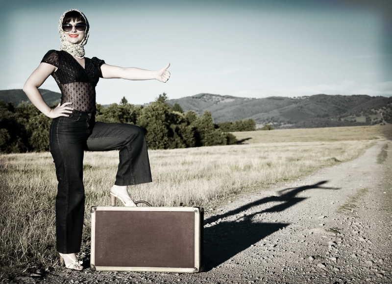 站在手提箱上拦车的美女