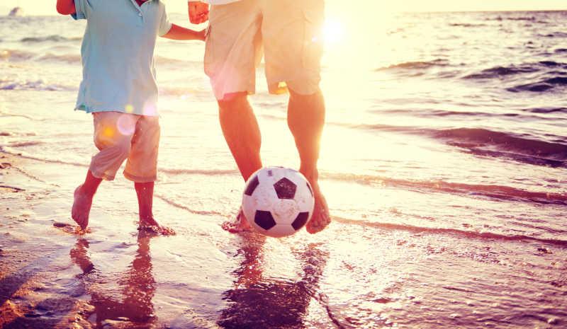 阳光下踢足球的父子