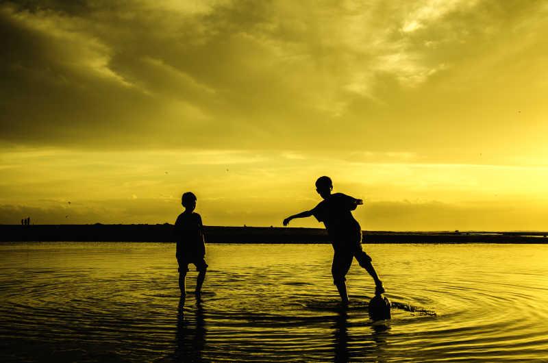 在沙滩上玩足球的男孩