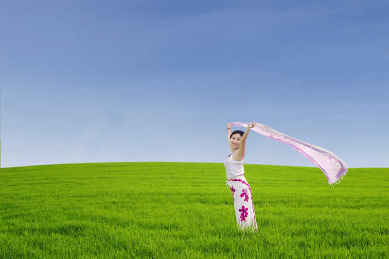 草原上放松心情的年轻女孩