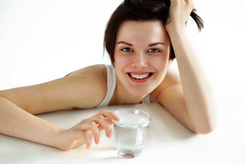可爱女孩拿着装满水的水杯