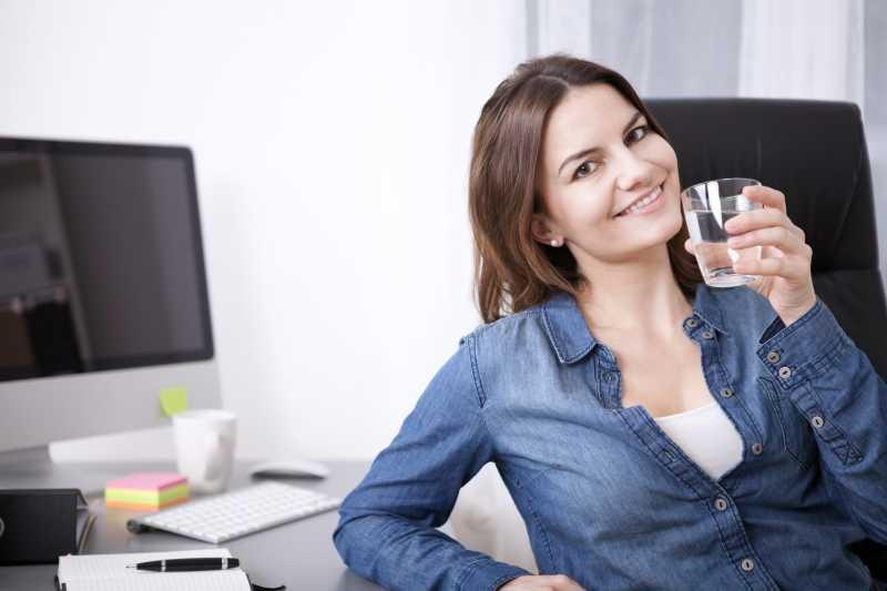 坐在椅子上喝水的办公室女商人