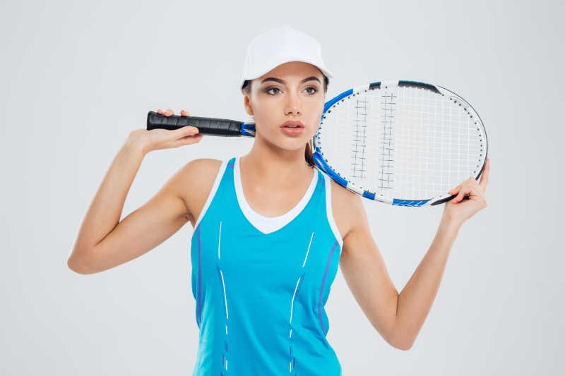 沉思的女运动员站在网球球拍的孤立在白色背景下载