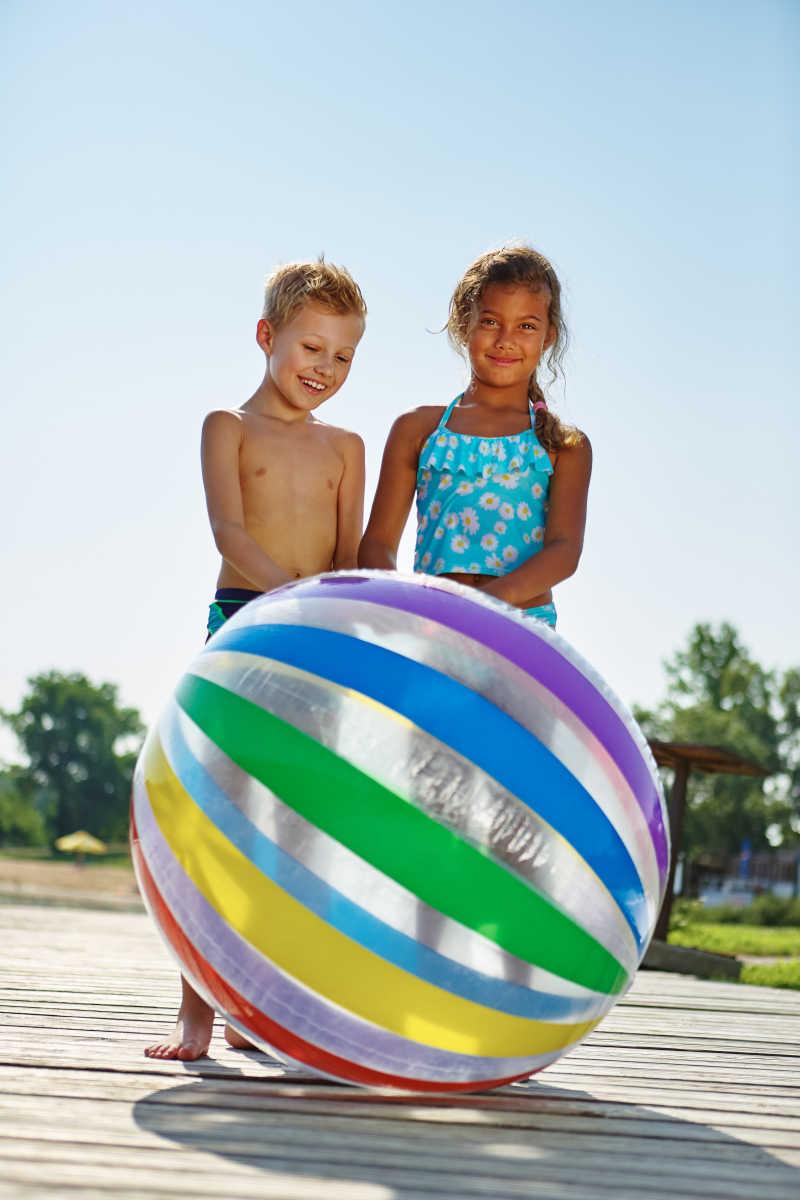 两个快乐的孩子在推一个大皮球