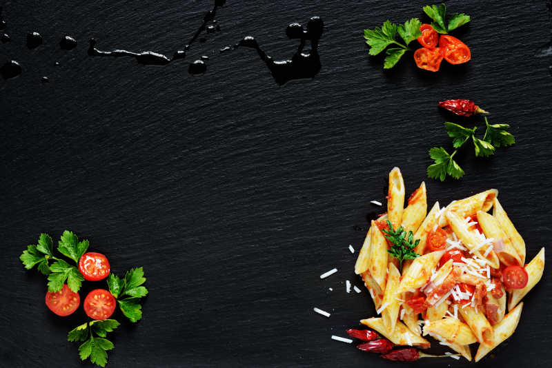 黑色桌子上的意大利面和番茄