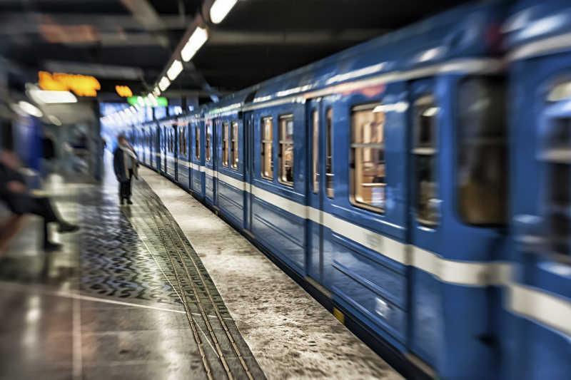 地铁站内行驶的蓝色地铁和乘客