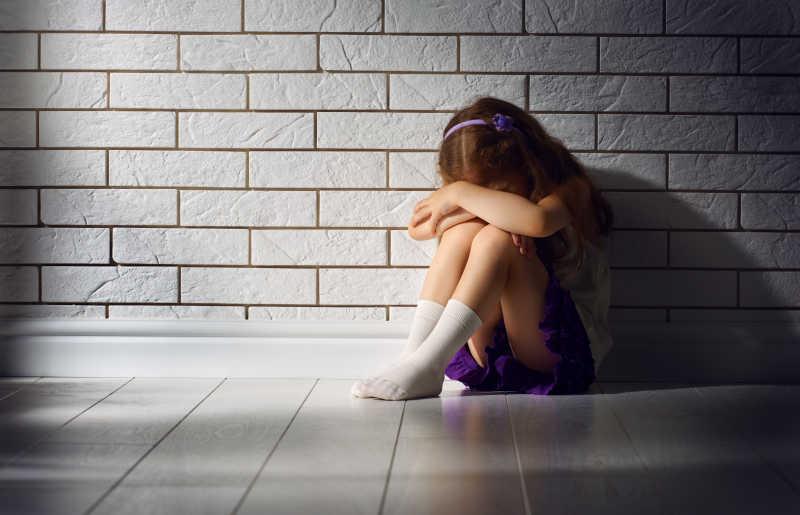 害怕的坐在墙边把头靠在膝盖上的女孩