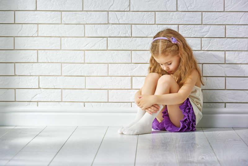 坐在墙边抱着双腿的金发女孩