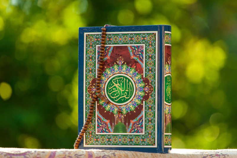放在户外的伊斯兰教圣书和珠链