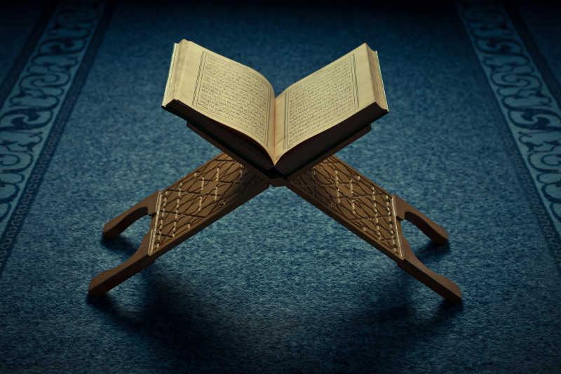 地毯上书架子上面有伊斯兰教圣书