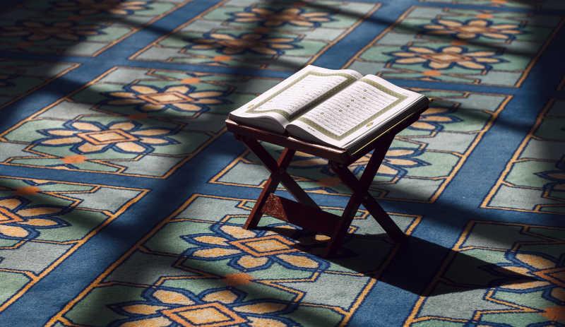 在室内地毯上的书架子和伊斯兰教圣书
