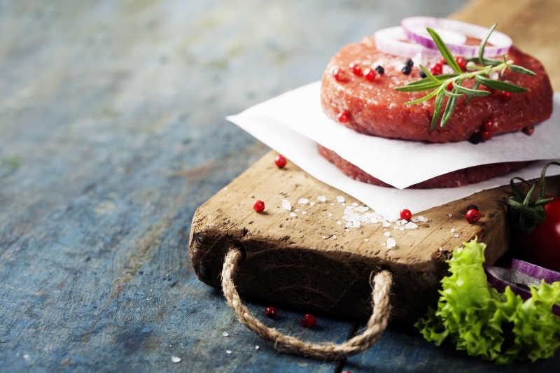 木板上撒着调料的牛排肉片