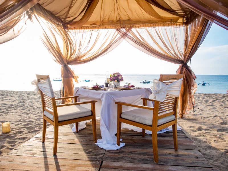 海滩上的晚餐餐具和桌椅