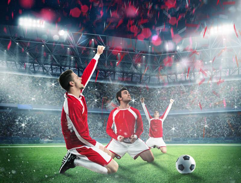 跪在足球场上庆祝胜利的三个男人