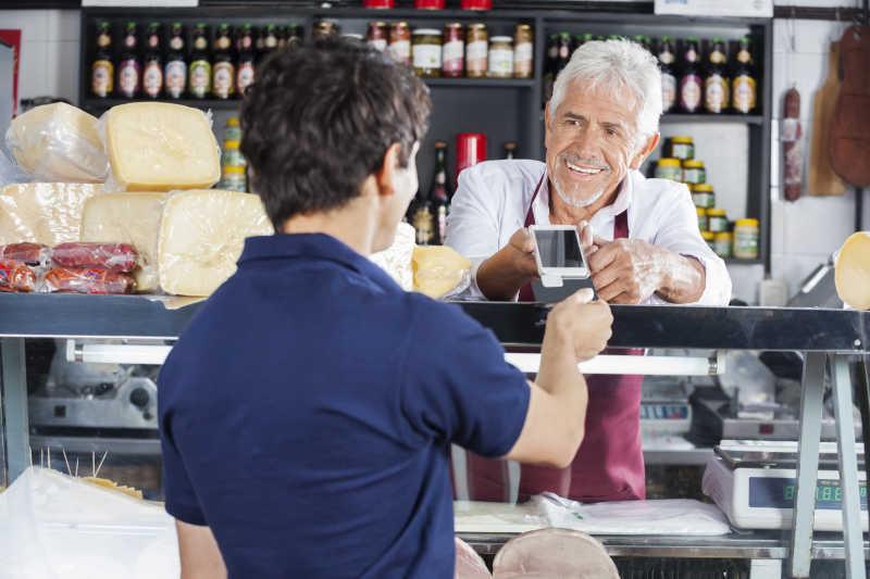 奶酪店里正在付款给售货员的顾客