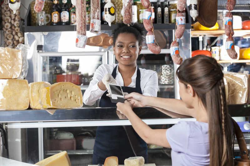 奶酪店里女售货员正在接受顾客的信用卡付款