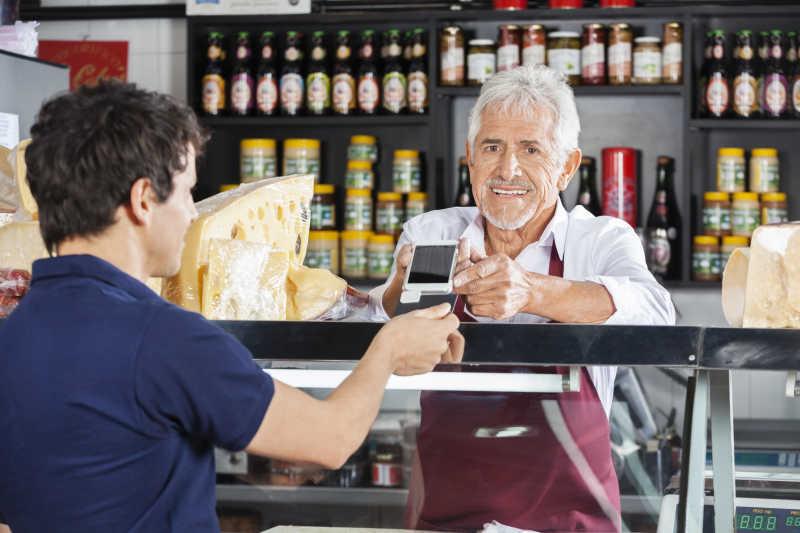 奶酪店里顾客和售货员正在用手机付款