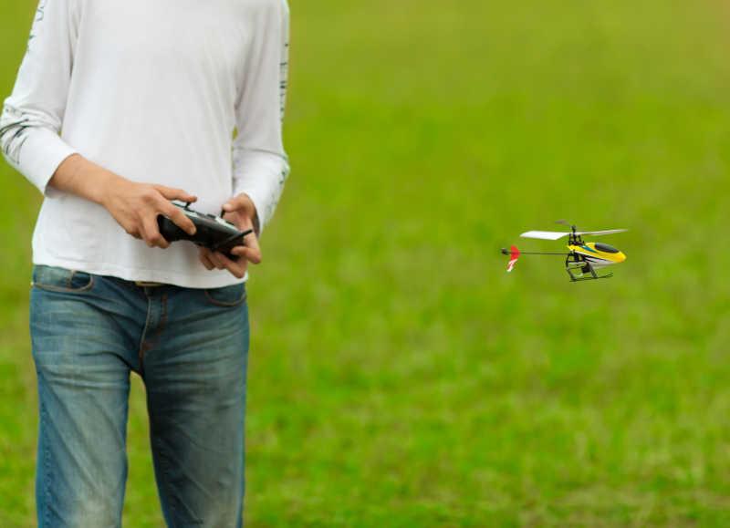 草地上年轻人拿着遥控飞机控制飞机模型飞行