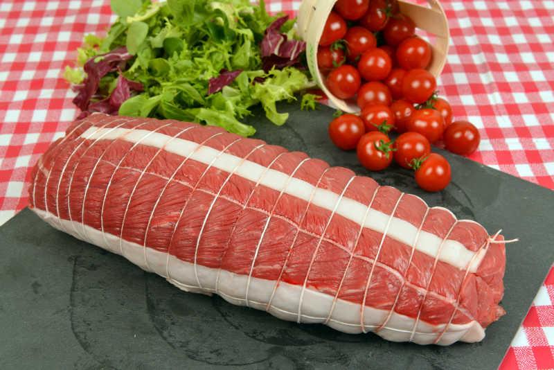 红色格子布上黑色案板上包装好的里脊肉