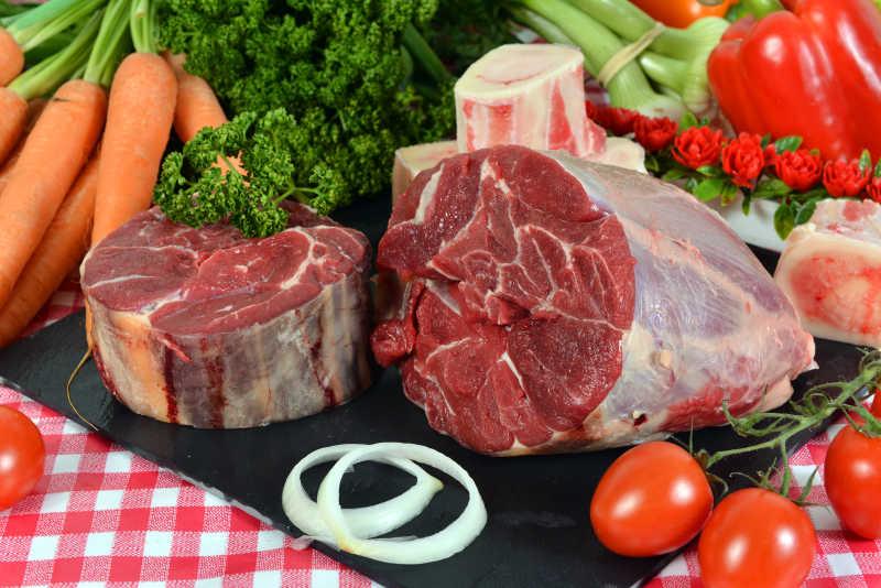 红色桌布上的一块红色的牛瘦肉和一些蔬菜