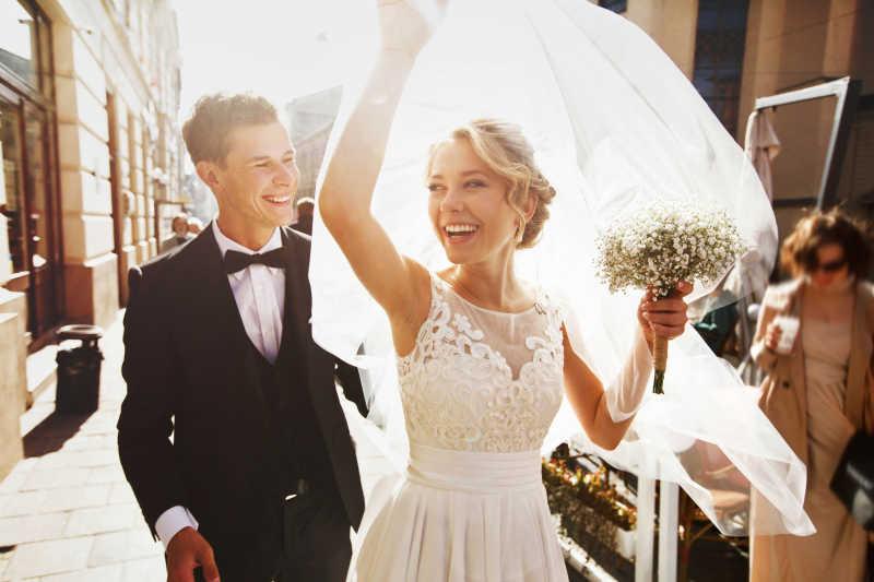 快乐的抓着头纱的新娘和幸福的新郎