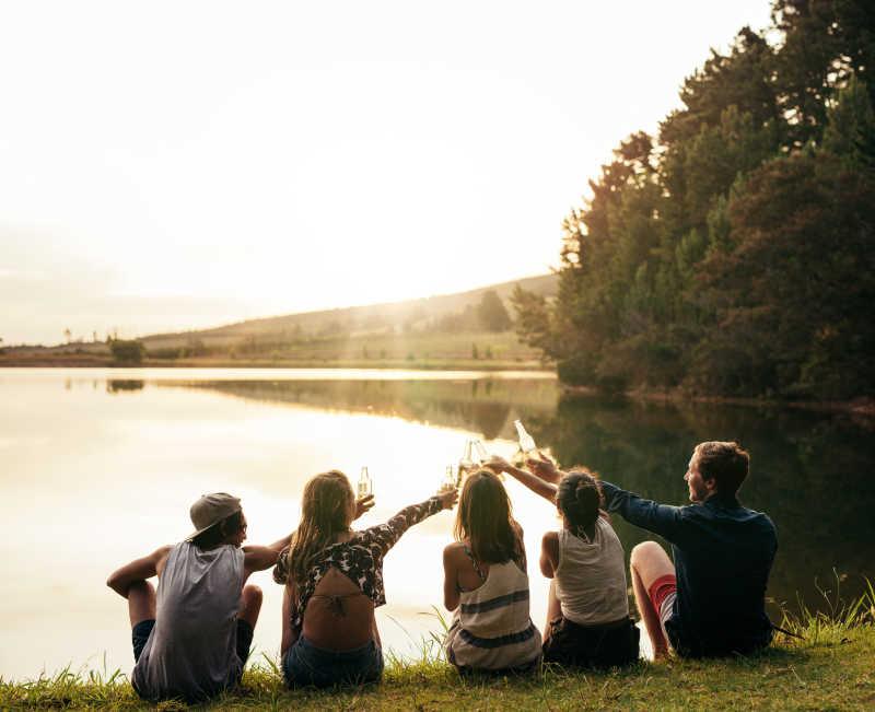 在湖边喝酒庆祝的年轻人